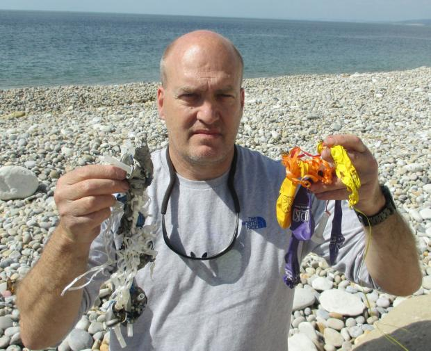 Dorset Echo: Environmental campaigner Steve Trewhella with balloons he has picked up from Dorset beaches over the years