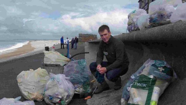 GOOD WORK: Dorset coastal ranger Tom Bennett with bags of rubbish collected from Chesil Cove