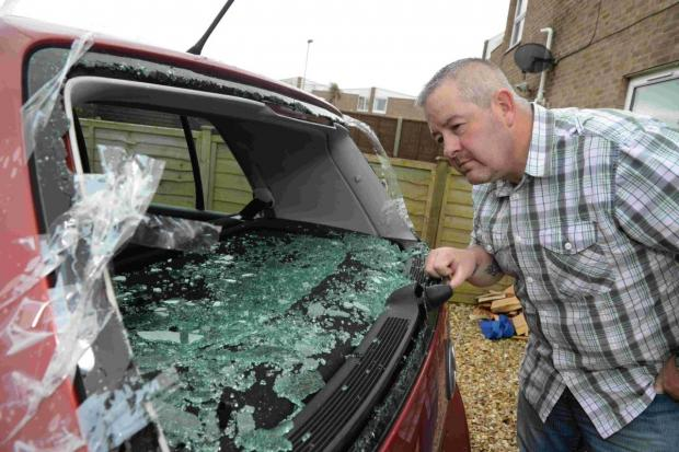 VICTIM: Andrew Denning inspects his damaged car