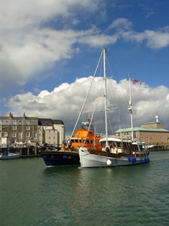 RESCUE: The boat is brought into Weymouth Harbour by the lifeboat. Picture: WEYMOUTH RNLI