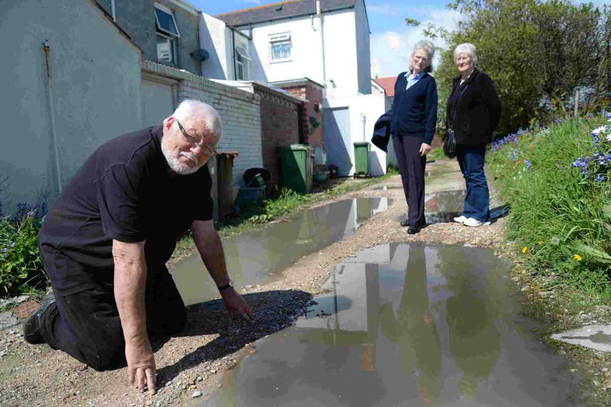 DAMAGE: Terry Hawker with other residents at Ferrybridge Cottages, upset they have been told to pay to repair road