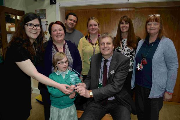 WELL DONE: Head Peter Farrington and pupil Eleanor Hedges receive an Epilepsy Award from Hattie Hodgson, left, from Epilepsy Action, watched by Eleanor's parents and school staff