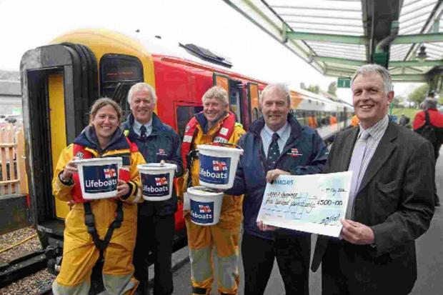 FUNDRAISING: Swanage railway volunteers present a cheque to the town's RNLI team to fund a new lifeboat house