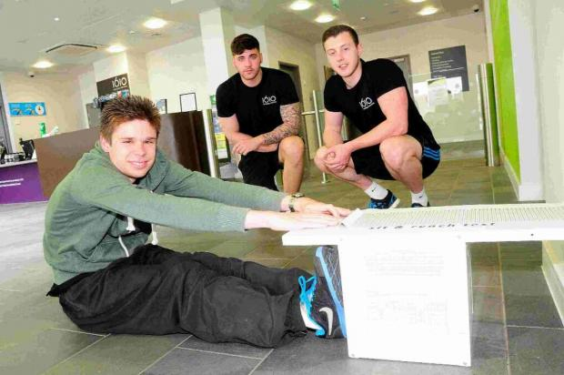 STRETCHING OUT: Chris Bartlett tries the Sit and Reach Test under the watchful eye of instructors Matthew Spicer and Connor Ryan
