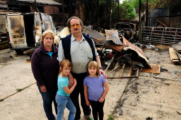 Dorset Echo: Farmer Brian Johnston and family with the fire damage