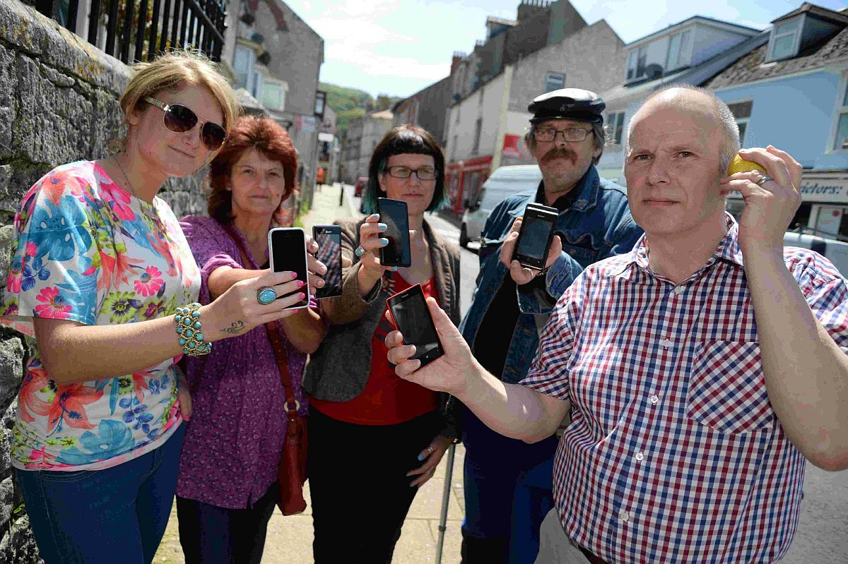 TRYING TO GET CONNECTED: Sarah Whiteside, centre, and Mark Jackson, right, join other residents in protesting against a lack of signal