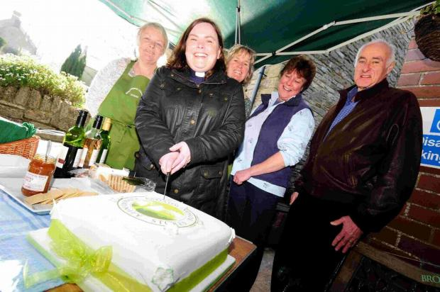 WELL DONE: Rev Jo Neary cuts the cake watched by Sue Williams, Mandy Crane, Jane Sloman and Fraser Hughes at the store's first anniversary earlier this year