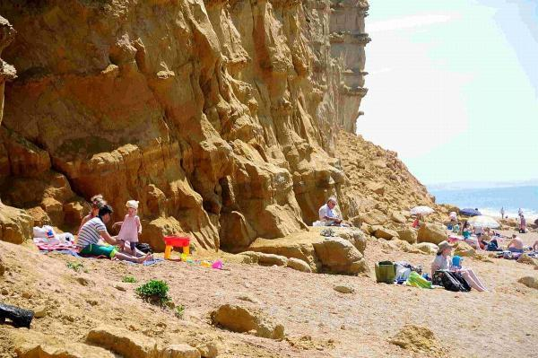 RISKY: Sunbathers risking their lives by sitting at the base of the cliffs on East Beach