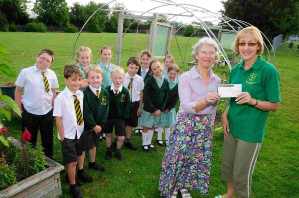Dorset Gardens Trust's Rosemary Agg presents the cheque to Gail Tucker and members of the school gardening club