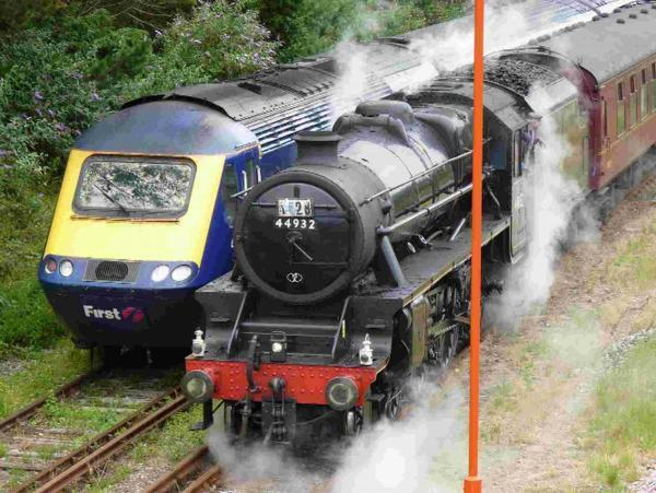 Steam locomotive alongside a high speed train. It comes from Bristol on summer Saturdays