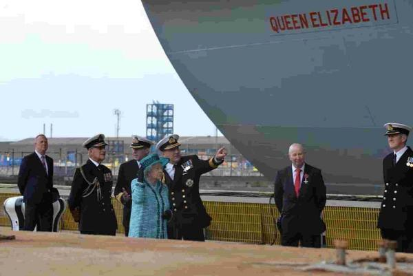 The First Sea Lord, Admiral Sir George Zambellas, pointing out some features of the Ship to Her Majesty The Queen, in front of Captain Simon Petitt speaking with Prince Phillip having just been introduced to The Queen