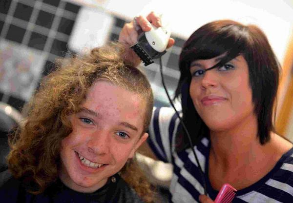 HAIR WE GO: Ethan Harwood at KCS Hair salon in Weymouth with Carly Drake halfway through his hair cut to raise money for the Deaf Children's Society