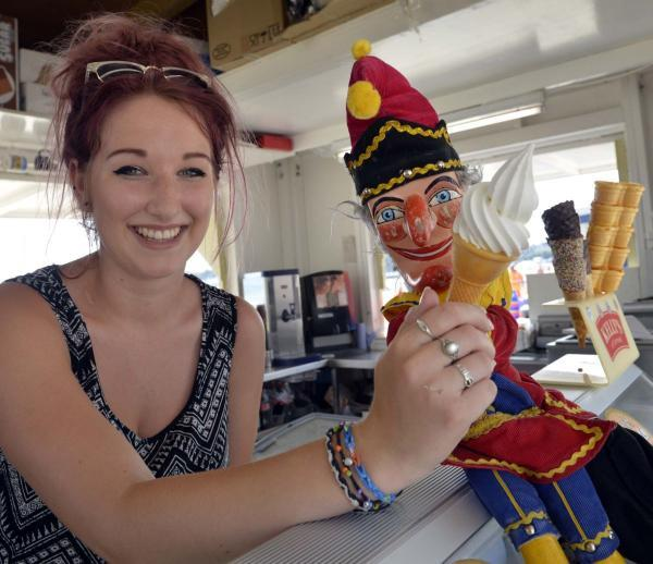 COOL: Mr Punch is served an ice cream on Weymouth Beach today by Emma Parsons (18).