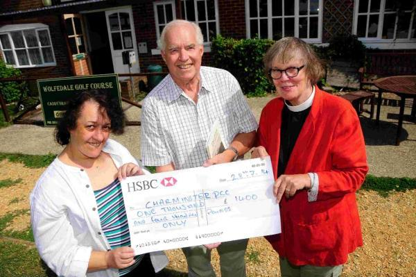 Alison Barlow presents the cheque for £1,400 to John Pearson and The Rev Janet Smith for the Charminster Church flood fund
