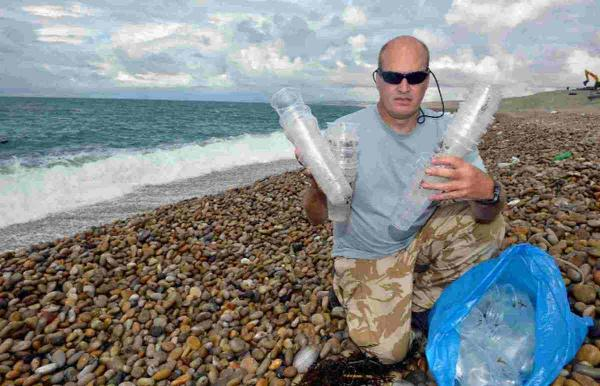 Steve Trewhella on Chesil Beach with just some of the hundreds of plastic cups that have washed up