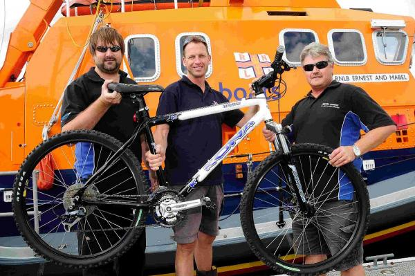 'OVERHWLEMED' RNLI crewman Alastair Heane, centre, gets his new bike from Ricol Leisure's Justin Camp, left, and Richard Jenkins, right