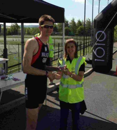 Bustinskin's Chris Walker is presented with his trophy for winning the Dorchester Triathlon by marketing manager for 1610,  Rebecca Sawtell
