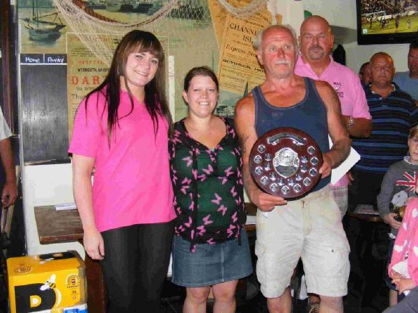 CHAMPION: Tony Denning collects his trophy from Holly Ankers, left, of Weymouth Angling Centre
