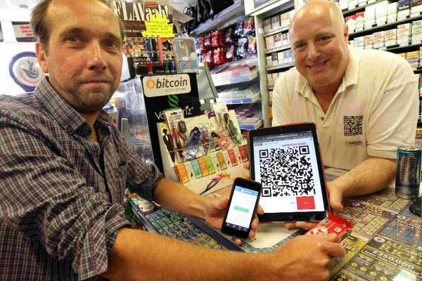 FUNDS: Andy James and Scott Green, left, who is a Bitcoin user and a smart phone and tablet which enables the payment process