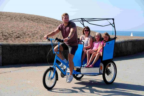 Jamie Stocks giving Carolyn Piggott, Sophie Moss and Abigail Piggott a ride in the rickshaw