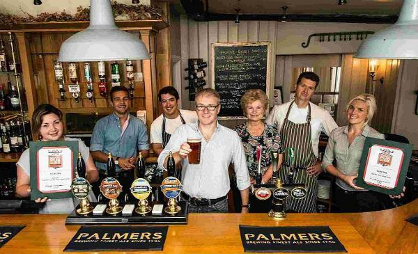 SIMPLY THE BEST: Landlord Jeremy Lee and the team at the New Inn, Cerne Abbas, behind the bar with the Good Pub Guide 2015 awards for Inn of the Year and Dorset Dining Pub of the Year