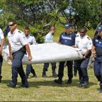 Dorset Echo: French police officers carry a piece of debris from a plane on Reunion island (AP)