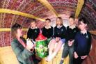 Specialist support worker Sarah Eaby shows a painted pot to pupils from Broadmayne First School in a traveller's caravan