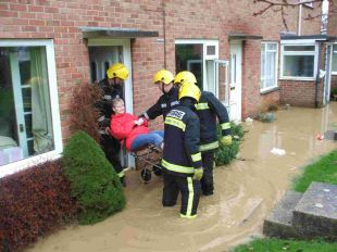MY SAVIOURS: Catherine Wright is rescued from her home by Weymouth firefighters	Picture: LAURA KITCHING