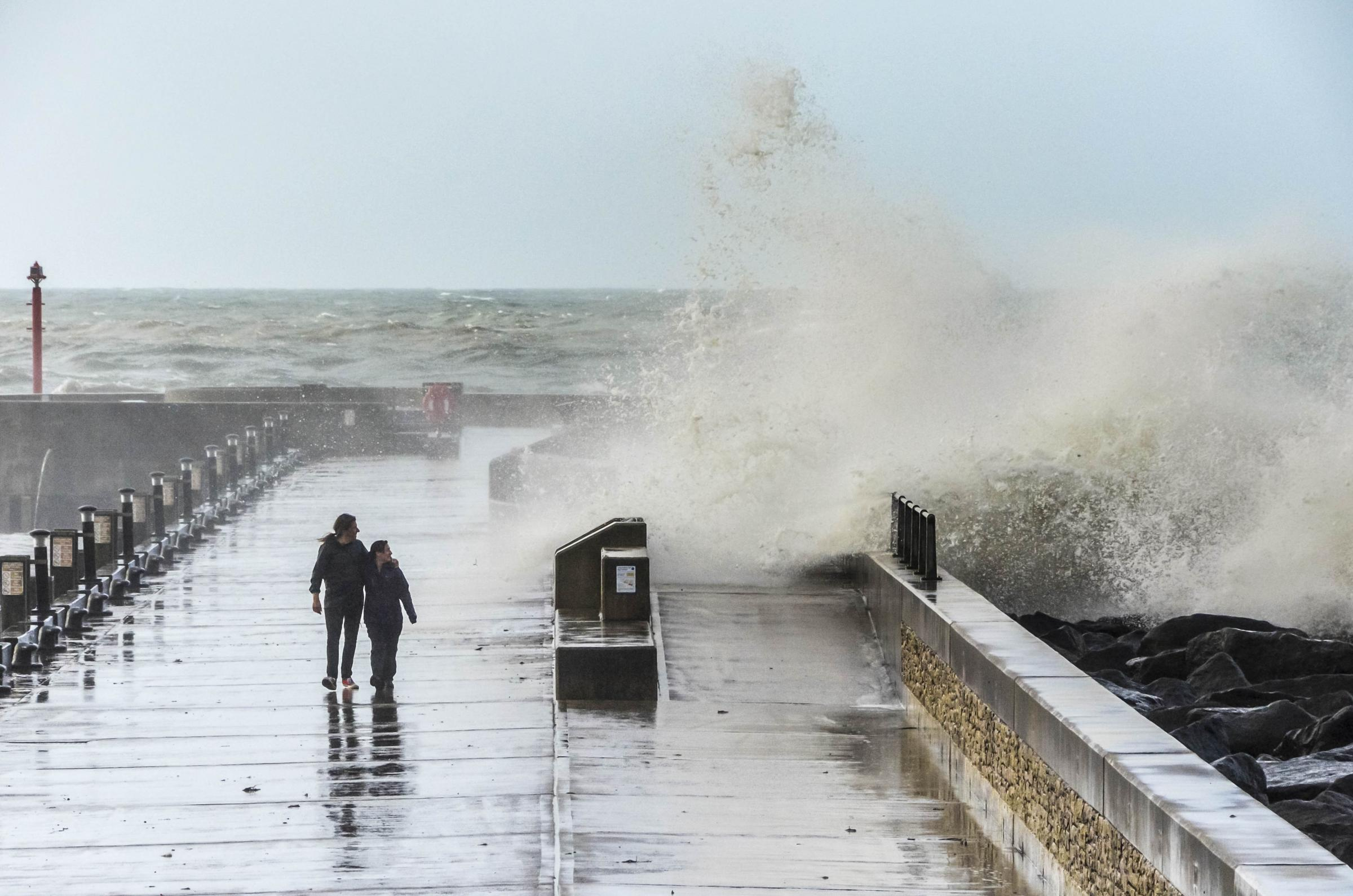 West Bay, Dorset, UK - 20th August 2016 - UK Weather.  A thrill seeking couple watching a wave crashing over the sea defences of the Jurassic Pier during a morning of rough seas and gale force winds which battered the costal resort of West Bay in Dorset d
