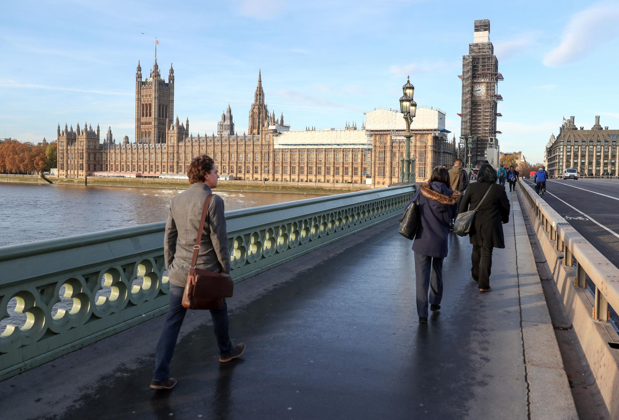 People walk across Westminster bridge next to the Houses of Parliament, London  Picture: Andrew Matthews/PA Wire