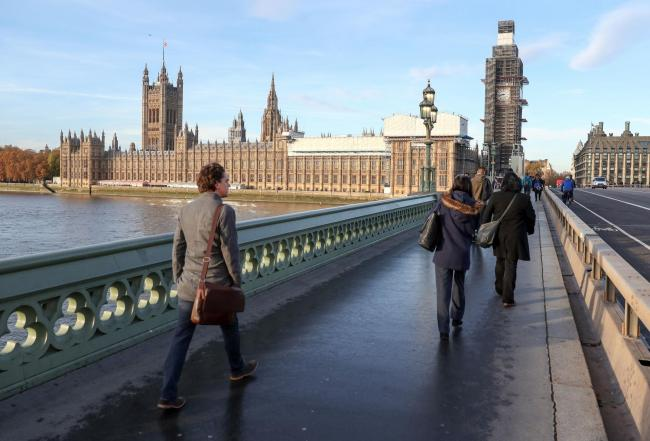 People walk across Westminster bridge next to the Houses of Parliament, London. PRESS ASSOCIATION Photo. Picture date: Wednesday November 14, 2018. Prime Minister Theresa May will put her Brexit plans to the Cabinet on Wednesday, 874 days after Britain vo