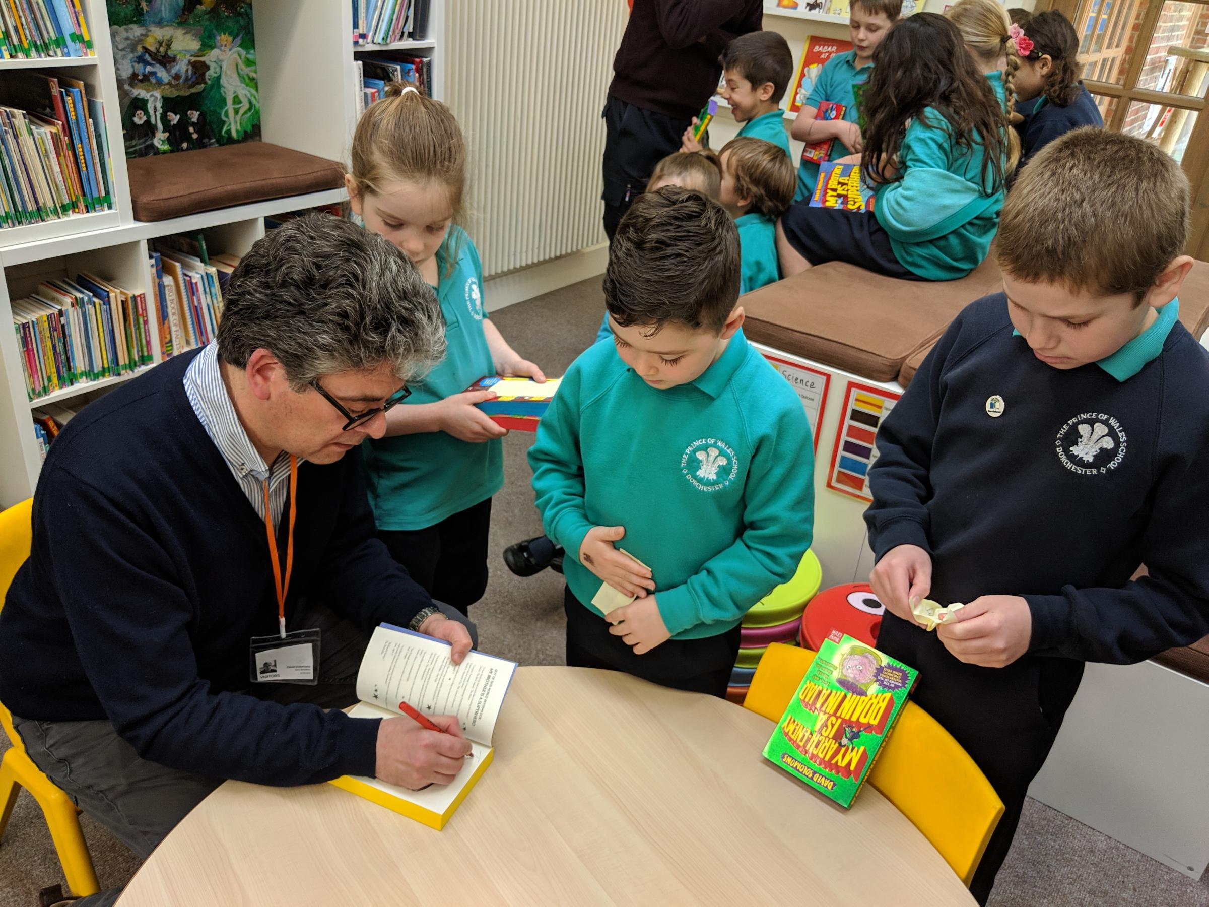 Children's author David Solomons signing copies of his books for the pupils