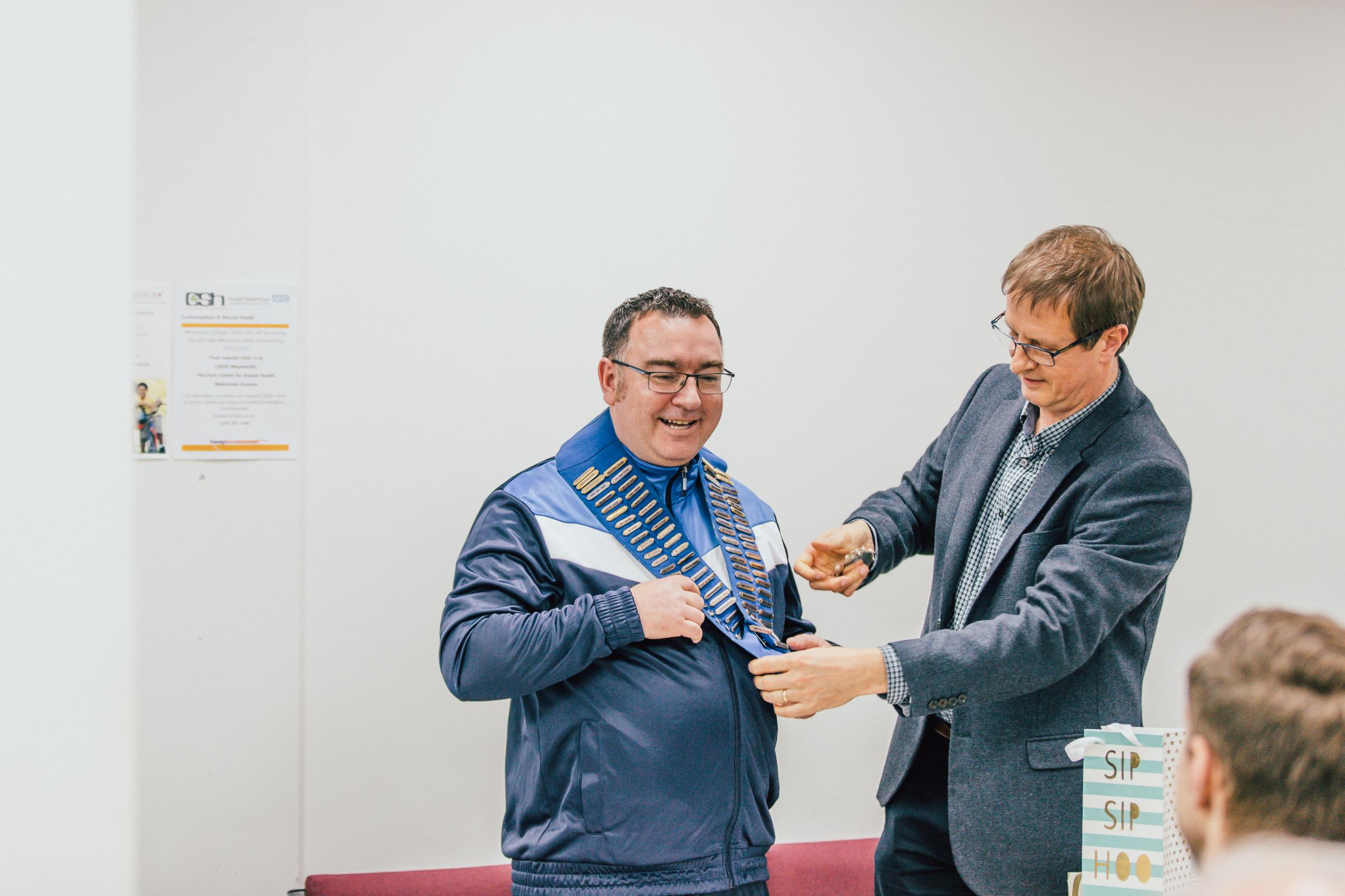 Pic from info@wpchamber.co.uk Craig Oakes, new president of Weymouth & Portland Chamber of Commerce, receives the chain of office from his predecessor, Andrew Knowles
