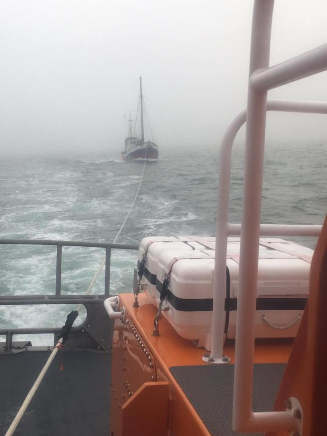 The motor cruiser being towed to safety. Photo: Weymouth Lifeboat