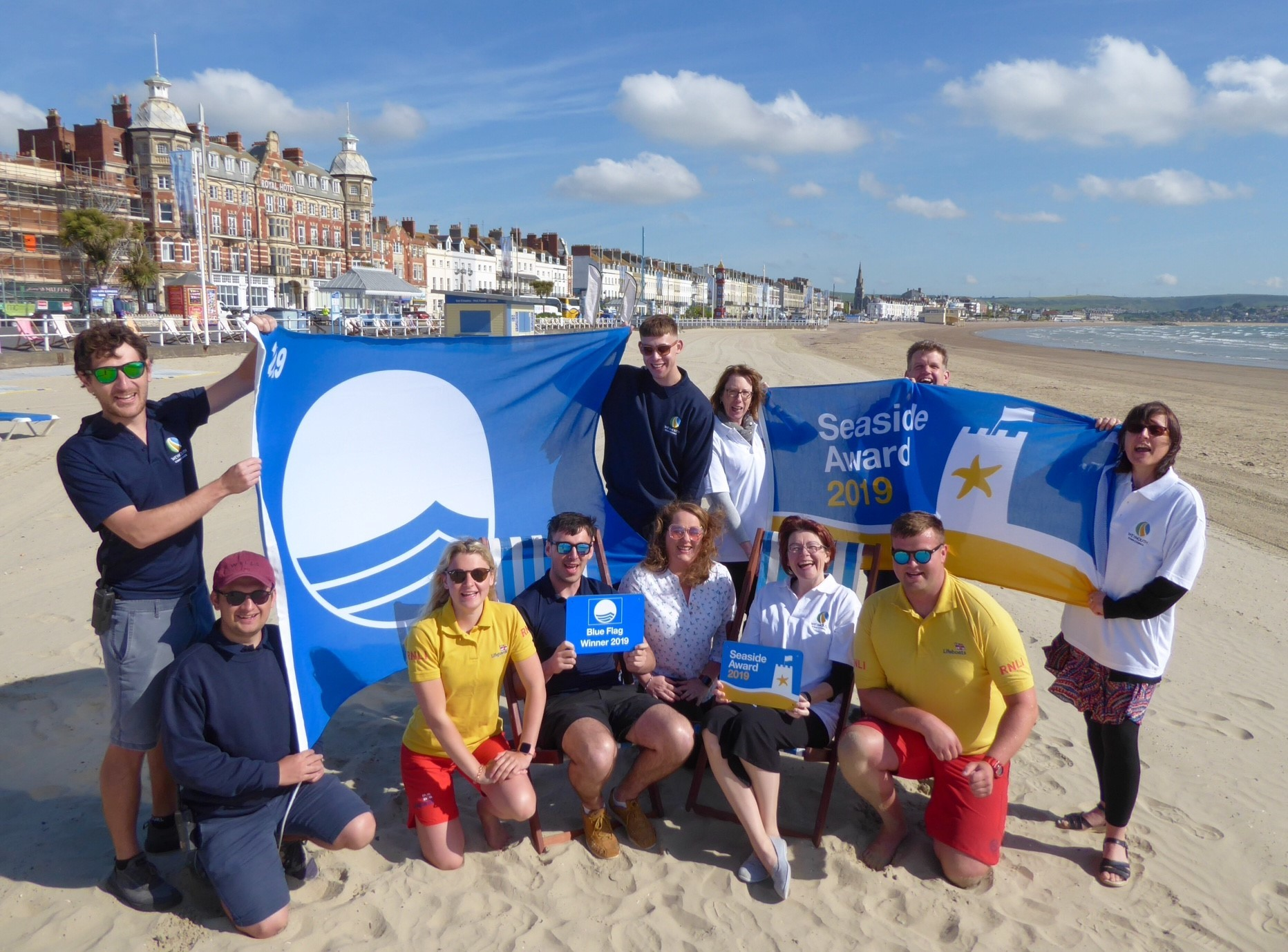 Weymouth Town Council Clerk Jane Biscombe is joined by Town Council Staff and Beach Lifeguards to celebrate the Blue Flag and National Seaside Award for Weymouth Beach